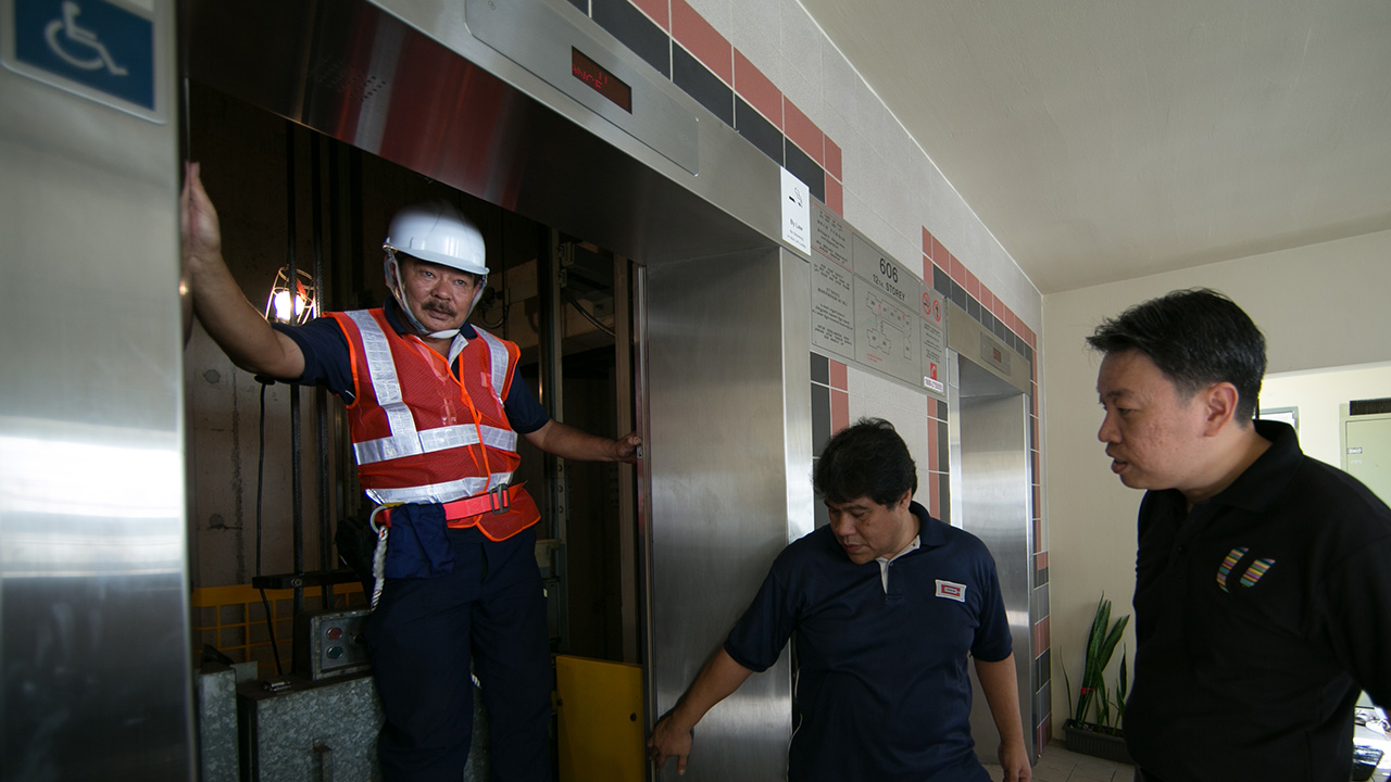 Having a quick chat with the lift technicians in between their servicing work (Photo Source: NTUC)
