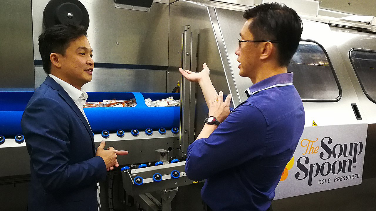 Managing Director of The Soup Spoon Andrew Chan demonstrating to Minister of State for Manpower Teo Ser Luck and attendees from the F&B industry how the HPP equipment works during a tour. (Photo: NTUC ThisWeek)