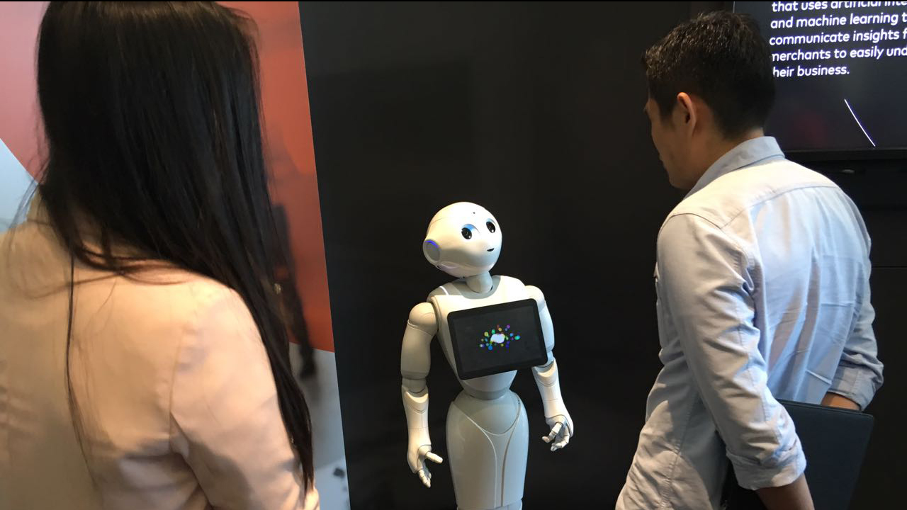 Participants interacting with a robot at the Innovation Exchange to Mastercard Labs.