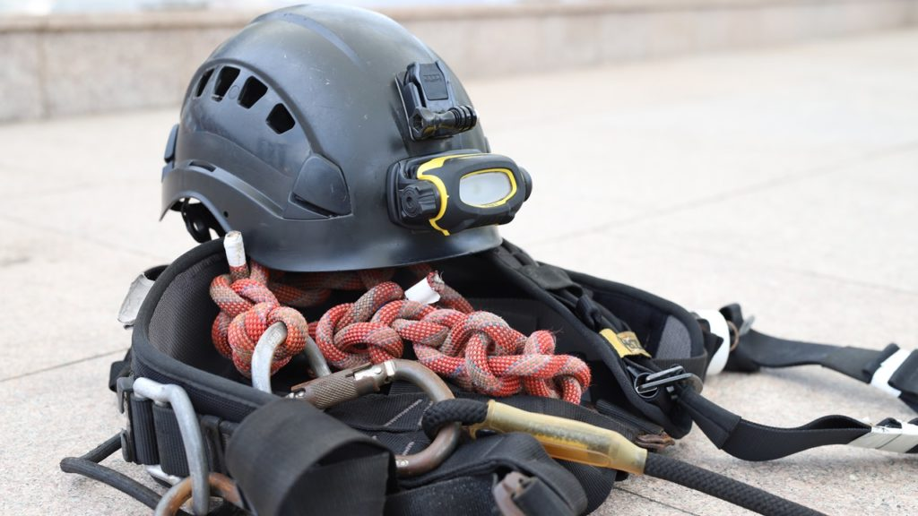 A rigger's safety gear includes a harness, helmet, and safety shoes.