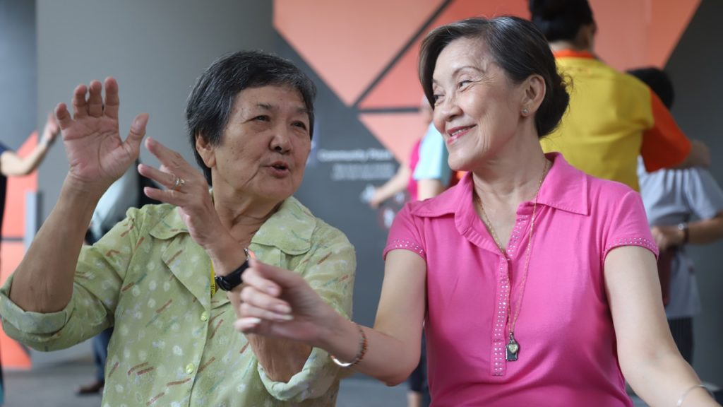 Mdm Hen (right) spends her time interacting with older, less mobile seniors from NTUC Health's senior care centre.